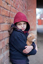 Homeless boy leaned against the wall with bear young Stock Image