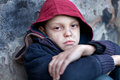 Homeless boy leaned against the wall young Royalty Free Stock Image