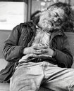 Homeless guy sleeping on a bench Stock Images