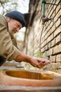 Homeless man washing hands in the street. Royalty Free Stock Photo