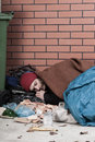 Homeless resting on the pavement vertical view of a Royalty Free Stock Photo