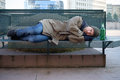 Homeless sleeping on the bench in the cold Royalty Free Stock Photo