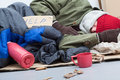 Homeless sleeping on the ground man cardboard with bag and thermos Stock Photo