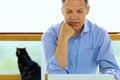 Homem caucasiano que olha seu laptop Fotografia de Stock Royalty Free