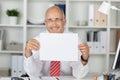 Homem de negócios feliz holding blank paper na mesa Imagens de Stock Royalty Free