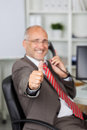 Homem de negócios gesturing thumbs up ao usar o telefone da linha terrestre Foto de Stock
