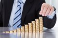Homem de negócios hand put coins à pilha de moedas Imagens de Stock