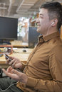 Homem de negócios listening music no escritório e no sorriso Imagens de Stock Royalty Free