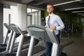 Homem de negócios running on treadmill no gym Fotografia de Stock