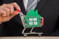 Homem de negócios holding shopping trolley com a casa do papel verde Foto de Stock