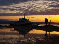 Homem e barcos no por do sol Fotografia de Stock Royalty Free