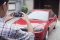 Homem novo que toma uma imagem de seu carro com seu telefone Fotos de Stock