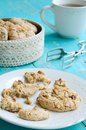 Homemade almond cookies and cup of tea with walnut on white plate placed on blue shabby wooden background Stock Image