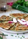 Homemade appetizing scallion pancakes with a bunch of green onions and radishes. Rustic style. Royalty Free Stock Photo