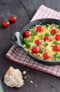 Homemade baked minced meat with cheese and cherry tomatoes topped chopped green onion in cast iron cooking pan on wooden Stock Images