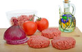 Homemade beef burgers chopping board tomatoes onion olive oil Royalty Free Stock Image