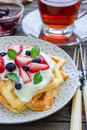 Homemade belgian waffles with yogurt, strawberry and blueberry, breakfast time Royalty Free Stock Photo