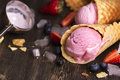Homemade berry ice cream portion of in wafer cone over grunge wooden table selective focus Royalty Free Stock Photography
