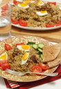 Homemade biryani a traditional indian beef served with hard boiled eggs tomato and cucumber with flat bread and a glass of water Stock Photo