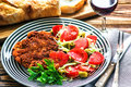 Homemade Breaded German Weiner Schnitzel and fresh vegetable spring salad with tomato, green olives, cabbage and parsley Royalty Free Stock Photo