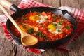 Homemade breakfast shakshuka of fried eggs with tomato close-up. Royalty Free Stock Photo