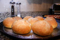 Homemade buns cooling down out of the oven with pizza in the background Royalty Free Stock Images