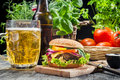 Homemade burger cold beer old wooden table Stock Image