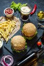 Homemade burgers with beef and fried potatoes and glass of cold dark beer on stone table Royalty Free Stock Photo