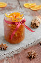 Homemade candied peels orange jam in glass jar confiture with spices cinnamon and anise star on rusted wooden background Royalty Free Stock Photo