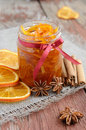 Homemade candied peels orange jam in glass jar confiture with spices cinnamon and anise star on rusted wooden background Stock Image