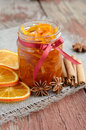 Homemade candied peels orange jam in glass jar confiture with spices cinnamon and anise star on rusted wooden background Stock Photo