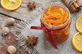 Homemade candied peels orange jam in glass jar confiture with spices cinnamon nutmeg and anise star on rusted wooden background Stock Image