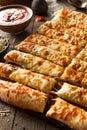 Homemade cheesy breadsticks with marinara sauce for dipping Royalty Free Stock Photos