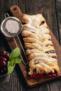 Homemade cherry puff pastry braid, on blue wooden background.