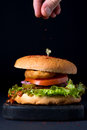 Homemade chicken burger on serving dark wooden board and man's fingers sprinkling red pepper Royalty Free Stock Photo