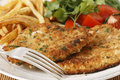 Homemade chicken schnitzels breaded or escalopes with french fries and a tomato and green salad Stock Photos