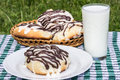 Homemade cinnabons cinnamon buns with cream cheese glaze and chocolate icing and  glass of milk Royalty Free Stock Photo