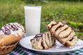Homemade cinnabons cinnamon buns with cream cheese glaze and chocolate icing and glass of milk. Royalty Free Stock Photo