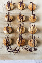 Homemade coconut macaroons with dripped dark chocolate on greaseproof paper Royalty Free Stock Photo