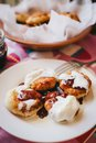 Homemade cottage cheese pancakes with jam and creamy sauce on a plate standing on a colorful tablecloth Stock Images