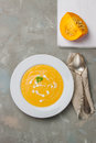 Homemade creamy pumpkin soup with cream and parsley in a white ceramic plate top view Royalty Free Stock Photography