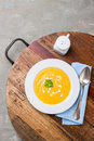 Homemade creamy pumpkin soup with cream and parsley in a white ceramic plate top view Stock Images