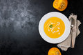 Homemade creamy pumpkin soup with cream and parsley in a white ceramic plate top view copy space Royalty Free Stock Photos