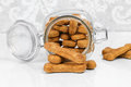 Homemade dog biscuits spilling from a glass canister healthy pumpkin on white table close up macro image Royalty Free Stock Photo