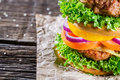 Homemade double decker burger with vegetables on old wooden table Stock Photography