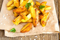 Homemade french fries fried potatoes with sea salt parsley and ketchup on paper and rustic wooden background Royalty Free Stock Photos