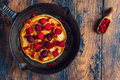 Homemade fried pancakes on a black cast iron skillet. Above are berries, raspberries, cranberries and blackberries. Royalty Free Stock Photo