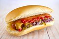 Homemade hotdog with ketchup mustard cucumber relish and red onion wood background Royalty Free Stock Photo