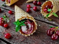 Homemade ice cream cherries and chocolate in a waffle cone, fresh cherries on old wooden table Royalty Free Stock Photo