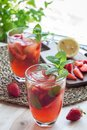 Homemade iced tea with strawberries and mint on wooden table, ve Royalty Free Stock Photo